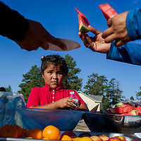 Carmen Martinez watches as others serve up a snack of fruits and other healthy options following a health walk in Pine Hill Thursday.