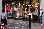 People wearing striped tops outside the spotted shop window of Urban Outfitters in central London.