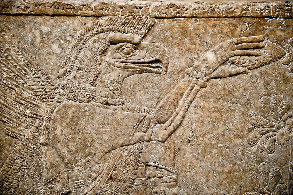 Assyrian relief sculpture panel  of an eagle headed protective spirit  from Nimrud, Iraq.  The spirit is holding a symbolic fir cone and is sprinkling holy water. 865-860 B.C North West Palace, Room F, panel 3.  British Museum Assyrian  Archaeological exhibit  ref WA 124584-5 .<br /> <br /> If you prefer to buy from our ALAMY PHOTO LIBRARY  Collection visit : https://www.alamy.com/portfolio/paul-williams-funkystock/ancient-assyria-antiquities.html  Refine search by adding background colour, place, subject, museum etc into the LOWER SEARCH WITHIN GALLERY box to <br /> <br /> Visit our ANCIENT ASSYRIAN PHOTO COLLECTIONS for more photos to download or buy as wall art prints https://funkystock.photoshelter.com/gallery-collection/Ancient-Assyrian-Art-Artefacts-Antiquities-Historic-Sites-Pictures-Images-of/C0000cjRqQyJjLag