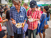 """07 AUGUST 2014 - BANGKOK, THAILAND: Men eat noodle soup provided by a Chinese foundation during a food distribution program at Pek Leng Keng Mangkorn Khiew Shrine in Bangkok. Thousands of people lined up for food distribution at the Pek Leng Keng Mangkorn Khiew Shrine in the Khlong Toei section of Bangkok Thursday. Khlong Toei is one of the poorest sections of Bangkok. The seventh month of the Chinese Lunar calendar is called """"Ghost Month"""" during which ghosts and spirits, including those of the deceased ancestors, come out from the lower realm. It is common for Chinese people to make merit during the month by burning """"hell money"""" and presenting food to the ghosts. At Chinese temples in Thailand, it is also customary to give food to the poorer people in the community.       PHOTO BY JACK KURTZ"""
