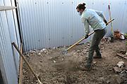 Nichole rakes area where my cistern pad will go.