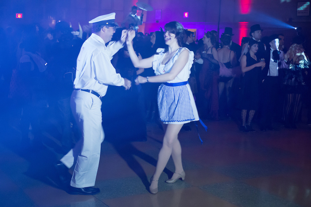 A couple costumed as a milkman and a milkmaid swing dance.
