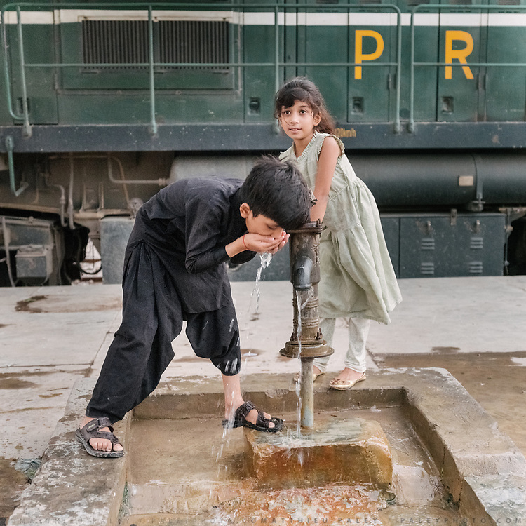 Brother and sister have a drink of water  during an evening outing at the train station.