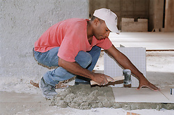 Construction worker in Havana Cuba working on the restoration of the Fine Art Museum  Museo de Bellas Artes; laying tiles,