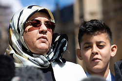 © Licensed to London News Pictures. 10/05/2018. London, UK. Fatima Boudchar (L), stood with her son, addresses the media outside Parliament after Attorney General Jeremy Wright announced that a settlement had been reached over her 2004 rendition to Libya. Fatima Boudchar and her husband, Abdel Hakim Belhaj, were kidnapped in Thailand in 2004 and flown to Libya in a rendition operation, allegedly with the help of MI6. Photo credit: Rob Pinney/LNP