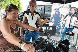 Laurie Schlenvogt of Harley-Davidson coaches Karen Keegan of Massachusettes in the Jumpstart area of the Harley-Davidson downtown display during the annual Sturgis Black Hills Motorcycle Rally. Sturgis, SD, USA. August 6, 2014.  Photography ©2014 Michael Lichter.