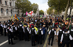 © Licensed to London News Pictures. 08/10/2019. London, UK. Large numbers of Police attempt to remove an Extinction Rebellion roadblock from Whitehall and move the remaining protesters to Trafalgar Square on the second day of protests in Westminster. Photo credit: George Cracknell Wright/LNP