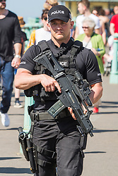 © Licensed to London News Pictures. 07/05/2018. Brighton, UK. Armed Police offers patrol the Brighton and Hove promenade. Thousands of visitors take to the beach in Brighton and Hove beach on the May Bank Holiday Monday as warm weather continues to hit the seaside resort. This weekend has been the hottest May Bank Holiday weekend on record. Photo credit: Hugo Michiels/LNP