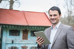 Portrait of a mature businessman using digital tablet outside and smiling, Bavaria, Germany
