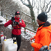 A 50 miles runner takes a short break at the top of the stairs to Jons Kapel.  Salomon Hammer Trail Winter Edition is a first on Bornholm and is one of the toughest routes in Denmark. The 4 runs consist of a 50 mile run, a marathon, a 1/2 marathon and 10k all run a on an approximate 25km route which includes 860 meter vertical rise on the North East coast of the Danish island Bornholm. The cut-off time for the 50mile run was 16 hours and more than a hundred runners made it to the finishing line. The last runner across the line after 50 miles  was in after 15:14:40