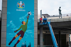 © Licensed to London News Pictures. 10/06/2021. LONDON, UK.  The Bobby Moore statue next to workmen installing signage around Wembley Stadium for the upcoming 2020 UEFA European Football Championship, commonly known as Euro 2020.  The tournament was postponed from 2020 due to the COVID-19 pandemic in Europe and rescheduled for 11 June to 11 July 2021 with matches to be played in 11 cities in 11 UEFA countries.  Wembley Stadium will host certain group matches including England v Croatia on 13 June, as well as the semi-finals and final itself.  Photo credit: Stephen Chung/LNP