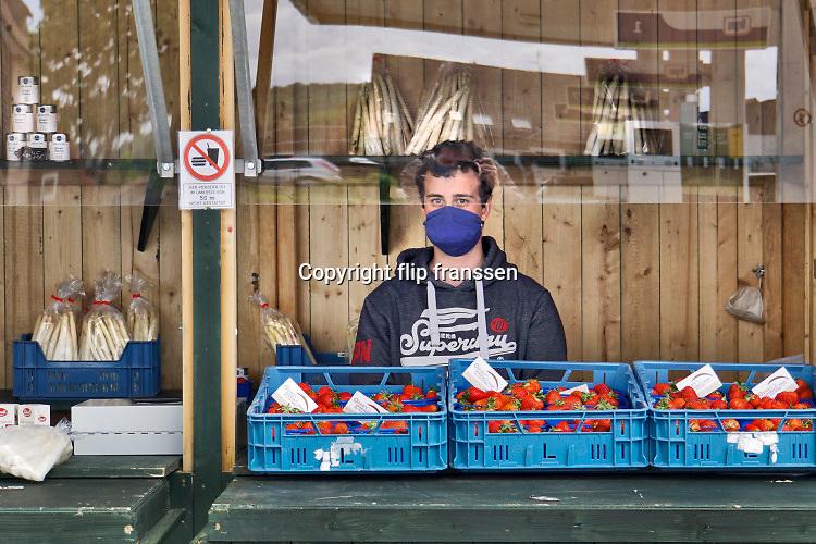Duitsland, Kranenburg, 1-5-2020  In Duitsland zijn in tegenstelling tot Nederland, mondkapjes verplicht in het openbaar vervoer en op plaatsen waar mensen te dicht bij elkaar kunnen komen. De jonge verkoper in deze kraam met asperges en aardbeien neemt geen risico . Foto: Flip Franssen