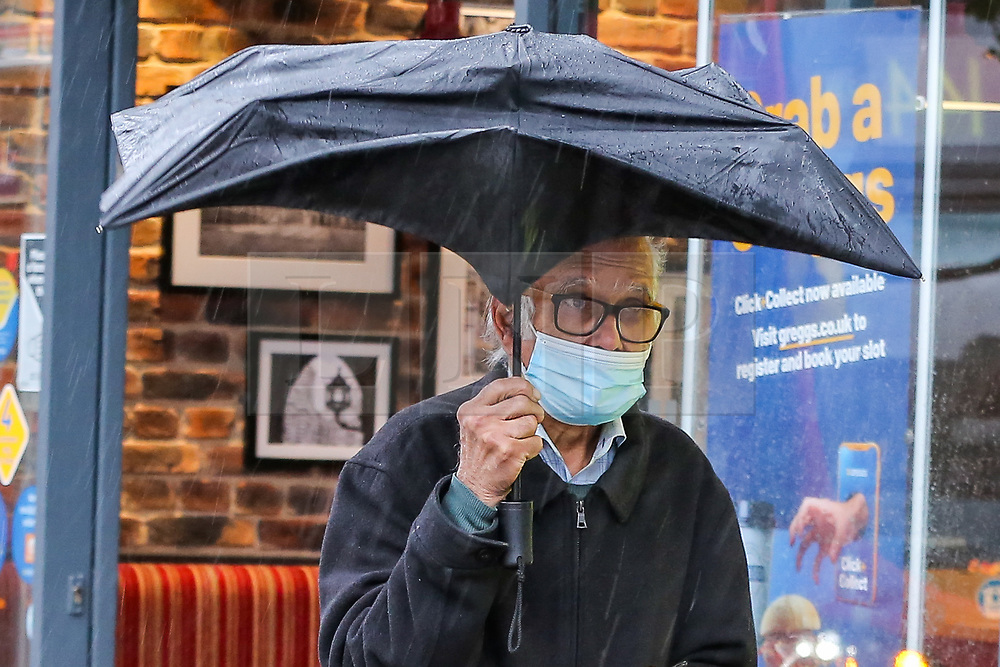 © Licensed to London News Pictures. 02/10/2020. London, UK. A man wearing a face covering shelters from rain underneath umbrellas in north London as Storm Alex arrives from Europe. The Met Office forecasts heavy rain and windy weather for the next few days in the capital, caused by Storm Alex. Photo credit: Dinendra Haria/LNP