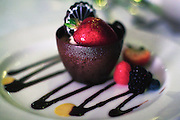 """A chocolate """"cup"""" dessert complete with berries, delicately drizzled with chocolate sauce."""