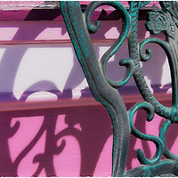 Antique-styled wrought iron chair with verdigris finish casting shadow on brightly colored pink wall.