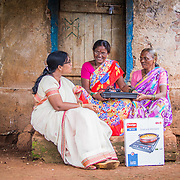 INDIVIDUAL(S) PHOTOGRAPHED: From left to right: Asha Anil Kamble, Mangal Lohar and Shalan Pandurang Lohar. LOCATION: Patan, Satara District, Maharasthra, India. CAPTION: Asha (left), a Dharma Life micro-entrepreneur, visits a neighbour's house to demonstrate the environmental and health benefits of using an electric cookstove. Leveraging its extensive network of locally-based entrepreneurs, Dharma Life has helped to address a variety of environmental, health, economic and social issues through the sale of products such as solar-powered lights, clean electric cookstoves, water filters, sewing machines and mobile phones.