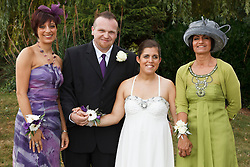 Bride who has cerebral palsy, with groom, her sister and her mother at wedding ceremony.