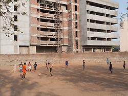 Young men playing football on land next to housing block being built in Mumbai