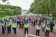 """Police officers form a line outside the HM Treasury building, as protestors dressed in Clown Circus march towards Trafalgar Square during an Extinction Rebellion protest called """"Corruption Carnival"""" in Westminster, central London on Wednesday, Sept 3, 2020. The environmental campaign group has planned events to be held at several landmarks in the capital. Extinction Rebellion plans to hold 10 days of demonstrations across central London as part of its ongoing campaign to highlight climate change. Environmental nonviolent activists group Extinction Rebellion enters its 3rd day of continuous ten days to disrupt political institutions throughout peaceful actions swarming central London into a standoff, demanding that the central government obeys and delivers Climate and Ecological Emergency Bill and prepare for crisis with a National Citizens' Assembly. (VXP Photo/ Vudi Xhymshiti)"""