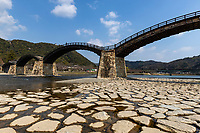 Kintai Bridge stands gracefully over the Nishiki River, and is a national treasure.  It was originally constructed in 1673. The wooden bridge with its dramatic 5 arches is an example of brilliant engineering it has been built and rebuilt numerous times due to flooding. The bridge was ultimately reconstructed with modern techniques after a small tax was implemented to assist with care and maintenance in its reconstruction of 2004.  At that time the arches were dismantled one by one to be transported and repaired offsite. Using the existing pieces as a template, the bridge was reconstructed to ensure everything fit properly, dismantled and then transported back to the bridge site and reassembled.
