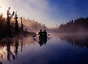 Karen Crosby and Scott Stolnack paddling canoe along shore of Loon Lake on a misty morning near Soldotna, Kenai Peninsula, Alaska.  (MR)