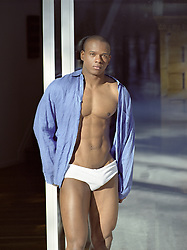 very good looking man in briefs and open shirt standing by a glass door