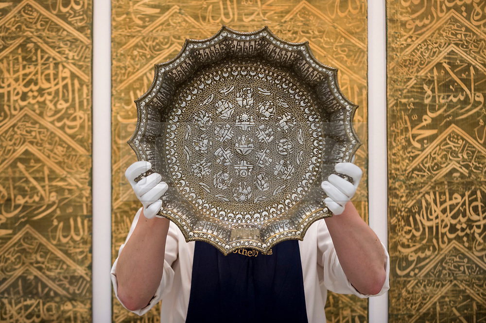"""© Licensed to London News Pictures. 29/03/2021. LONDON, UK. A technician presents """"a magnificent twelfth-century silver-inlaid scalloped basin adorned with astrological designs"""" (est. £1,000,000-1,500,000).  Preview of the upcoming Arts of the Islamic World & India sale where historic objects, paintings and manuscripts from the last 1,000 years are to be auctioned on 31 March at Sotheby's New Bond Street galleries.  Photo credit: Stephen Chung/LNP"""