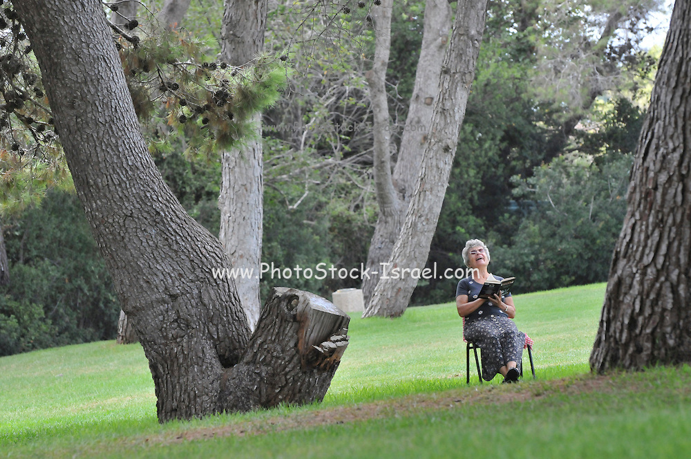 A mature woman sit on a chair in the park and reads a book