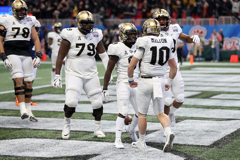 UCF Knights quarterback McKenzie Milton (10) celebrates a touchdown during the 2018 Chick-fil-A Peach Bowl NCAA football game against the Auburn Tigers on Monday, January 1, 2018 in Atlanta. (Jason Parkhurst / Abell Images for the Chick-fil-A Peach Bowl)