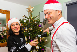 Mike pours Miriam a glass of bubbly in front of the Christmas tree. Brighton, December 16 2018.