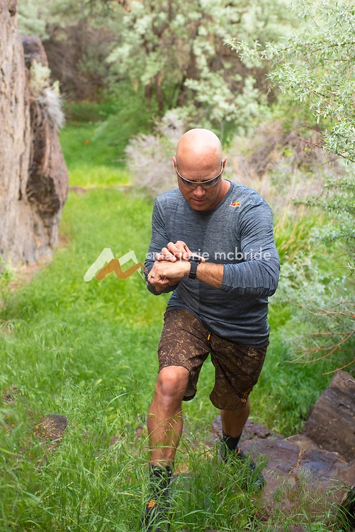 Man checking sport watch while hiking in the canyon, Twin Falls, Idaho. MR