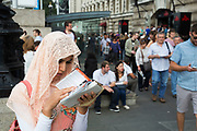 An Asian woman tourist wearing a peach coloured headscarf looks at her map to figure out which way to go. The South Bank is a significant arts and entertainment district, and home to an endless list of activities for Londoners, visitors and tourists alike.