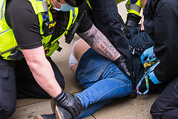 """© Licensed to London News Pictures. 27/03/2021. Manchester, UK. A police officer with """" Non illegitimi carborundum est """" tattooed on his arm - which is translated as """"Don't let the bastards grind you down"""" holds a woman down as she is detained by several officers . Police move in to remove and detain protesters who were sitting on and blocking tram tracks in St Peter's Square in Manchester City Centre . """" Kill the Bill """" and Reclaim the Streets demonstrations are held in Manchester City Centre in opposition to the Police, Crime, Sentencing and Courts Bill 2021 that is currently before Parliament and after the death of Sarah Everard in London . Photo credit: Joel Goodman/LNP"""
