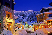 Town Plaza, with Blackcomb Mountain rising behind, on a snowy winter evening. Whistler, BC