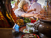 """07 AUGUST 2014 - BANGKOK, THAILAND: A woman leaves ceremonial food at an alter Pek Leng Keng Mangkorn Khiew Shrine. Thousands of people lined up for food distribution at the Pek Leng Keng Mangkorn Khiew Shrine in the Khlong Toei section of Bangkok Thursday. Khlong Toei is one of the poorest sections of Bangkok. The seventh month of the Chinese Lunar calendar is called """"Ghost Month"""" during which ghosts and spirits, including those of the deceased ancestors, come out from the lower realm. It is common for Chinese people to make merit during the month by burning """"hell money"""" and presenting food to the ghosts. At Chinese temples in Thailand, it is also customary to give food to the poorer people in the community.     PHOTO BY JACK KURTZ"""