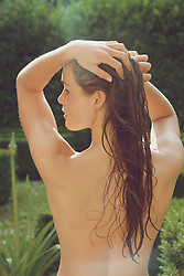 Back View of Nude Woman with Wet Hair in Garden