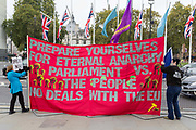 Two Brexiters in Parliament Square mind a large banner warning of eternal anarchy, a confrontation between the British parliament and the British people during a political climate of anger and mistrust of members of parliament and parliamentary democracy by those wanting Brexit, during Prime Minister Boris Johnson's Brexit deal negotiations with the EU in Brussels, on 23rd October 2019, in Westminster, London, England.