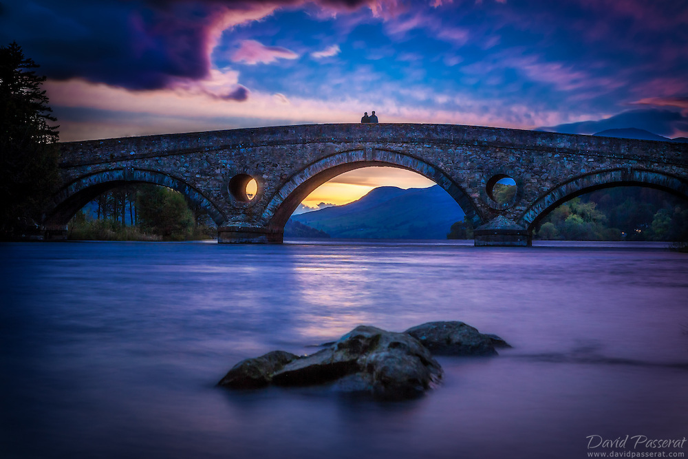 Kenmore bridge view from the shore.<br /> Kenmore (Gaelic: A' Cheannmhor) is a small village in Perthshire, in the Highlands of Scotland, located where Loch Tay drains into the River Tay.
