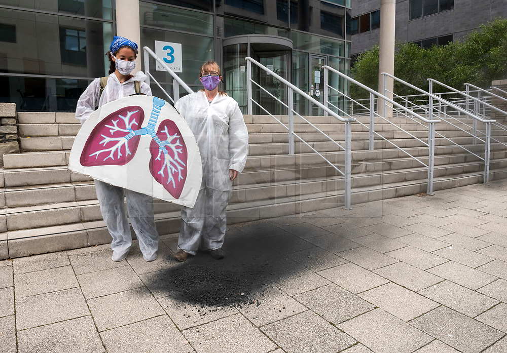 """© Licensed to London News Pictures;27/06/2020; Bristol, UK. Extinction Rebellion end a week of protests by dumping soot from a giant pair of lungs onto the steps of the headquarters of the West of England Combined Authority (WECA) as the over-arching regional authority in the area. Extinction Rebellion's Five a Week campaign for clean air is highlighting the number of premature deaths in Bristol due to air pollution. They set up 296 pairs of shoes on College Green in front of City Hall with the message """"296 Deaths a Year"""" which the campaigners say is the number of people who die each year due to air pollution in the city. On Thursday five Extinction Rebellion activists climbed up the central dome of Bristol City Hall and say they will stay up there until Bristol City Council commits to ensuring legally clean air in every suburb of the city by April 2021. Extinction Rebellion demand urgent action from Bristol City Council & WECA (West of England Combined Authority) to protect people's lungs and protect the planet, saying health is intrinsically linked to the health of the environment. XR want Clean Air Equality for Life, not just for the coronavirus Covid-19 lockdown, saying there is a unique opportunity as we come out of lockdown to envision a Bristol that puts people's health and the health of the planet first, and put pressure on elected officials to help build the city back better. Photo credit: Simon Chapman/LNP."""