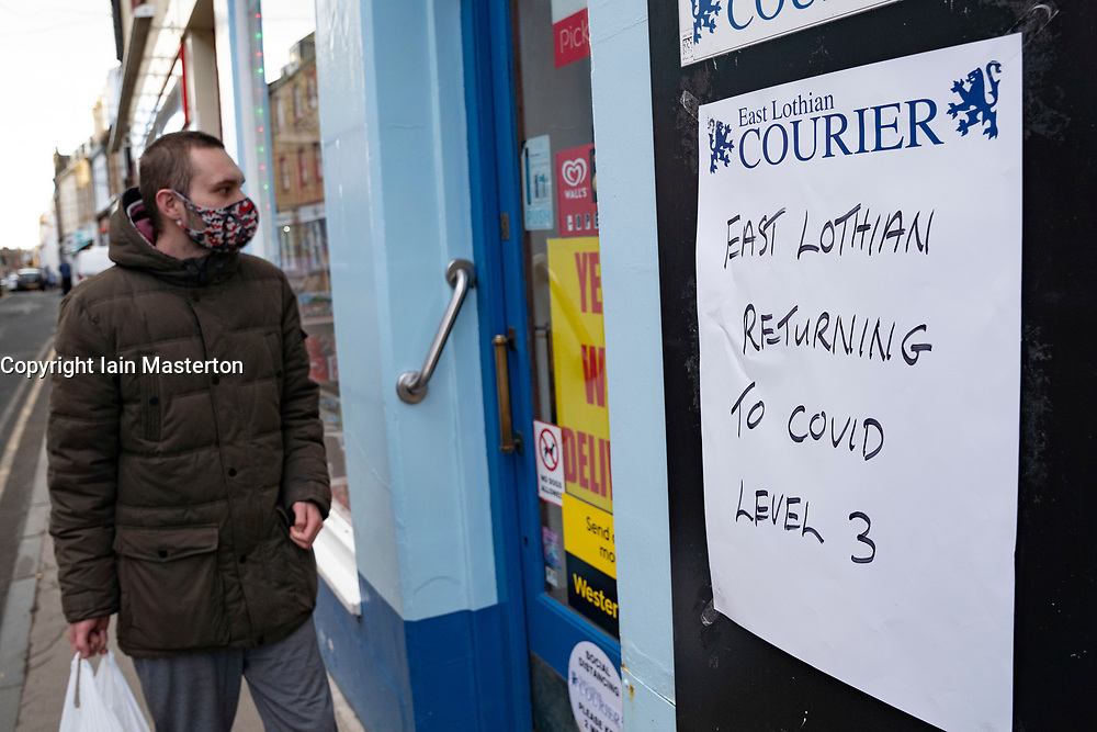 North Berwick, Scotland, UK. 17 December 2020. Scottish Government states that East Lothian is to move from level 2 to level 3 lockdown from Friday 18 December. This means restaurants and bars are not allowed to sell alcohol. Pic;  Sign outside newsagent shop  informing public of return to level 3 lockdown.  Iain Masterton/Alamy Live News