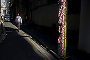 A man wearing matching red tie approaches a sunlit post and warning tape in a City of London street.