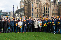 Westminster, London, October 14th 2015. Members of the FBU gather outside Parliament as they prepare to lobby MPs over cuts, the Trade Union Bill and the possibility of their service falling under the control of Police and Crime Commissioners. PICTURED: FBU Members pose for a group shot as they prepare to enter Parliament.