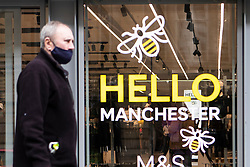 © Licensed to London News Pictures. 20/10/2020. Manchester, UK. A man wearing a mask walks past a sign on Market Street in Manchester which reads, 'Hello Manchester'. Manchester is expecting to be forced in to a Tier 3 lockdown unless a deal is agreed. Photo credit: Kerry Elsworth/LNP