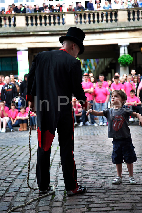 Covent Garden in the West End of London. Street performer interracts with a young member of the audience as part of his act.