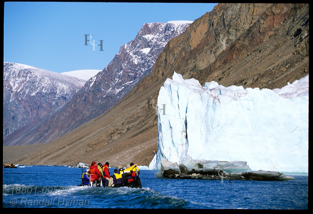 Rubber Zodiac raft approaches massive foot of glacier protruding into Dexterity Fjord; Baffin Island, Nunavut, Canada