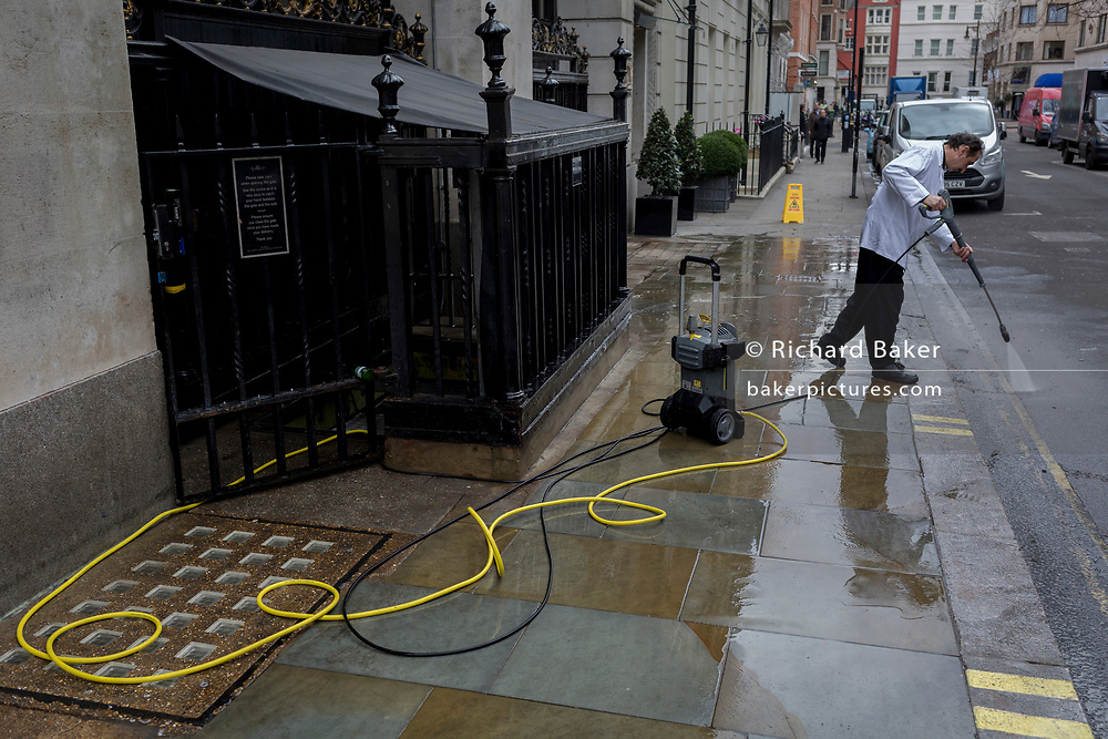 After a week of snow and ice, an employee uses a pressure hose to wash down a dirty pavement at the side entrance of the Wolseley Brasserie opposite the Ritz in Arlington Street, on 5th March 2018, in London, England.