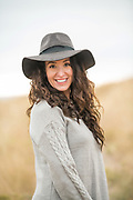 Natural portrait of a woman wearing a hat and a beige sweater