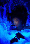 A young woman lying down with her her spread across a glowing veil.Black light