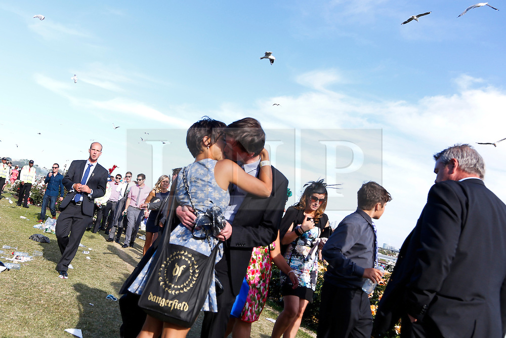 © Licensed to London News Pictures. 5/11/2013. A couple kiss as passers by leave at the end of the day during Melbourne Cup Day at Flemington Racecourse on November 5, 2013 in Melbourne, Australia. Photo credit : Asanka Brendon Ratnayake/LNP