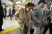 elderly couple entering a train Tokyo Japan